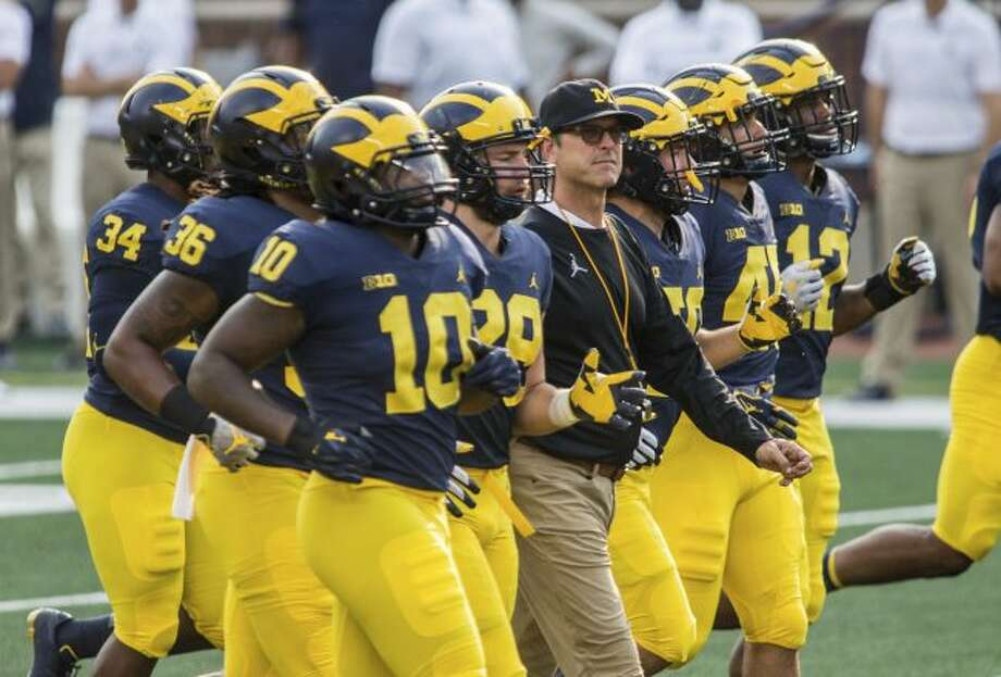 In this Sunday, Aug. 26, 2018, file photo, Michigan head coach Jim Harbaugh, center, walks the field as players jog around him during an open practice for the NCAA college football team at Michigan Stadium in Ann Arbor, Mich. Michigan plays Notre Dame on Saturday, Sept. 1, to open the college football season. (AP Photo/Tony Ding, File)
