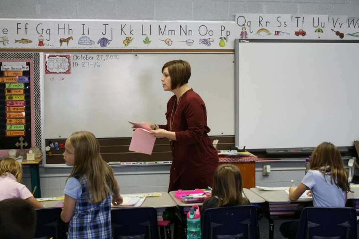 Angela Denny passes out papers in her second grade class at St. Mary Catholic School in Big Rapids in this October 2016 file photo. (Pioneer file photo)