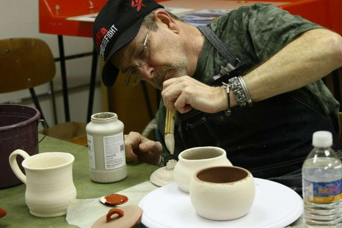 CAREFUL MOVEMENTS: Chuck Briggs carefully paints a lid he made, which matches one of the pots he created over the six-week workshop.(Pioneer photos/Meghan Haas)