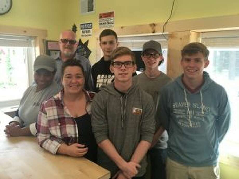 Scott and Angela Findley — first from left in back and second from left in front, respectively — pose with their children Matthew, Nicolas, Timothy, Daniel and Kayla at the restaurant they opened outside of Newaygo, The Jetty. (Pioneer photo/Tim Rath)
