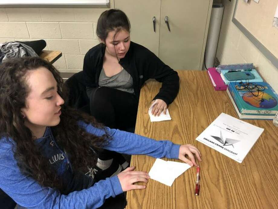 (From left) Morley Stanwood Middle School students Emma Garlick and Kadence Harris fold origami cranes in hopes to create 1,000 of the paper birds to make a wish for good health for a classmate. Garlick and Harris are two of the many students from sixth through eighth grade who folded the cranes. (Courtesy photo)