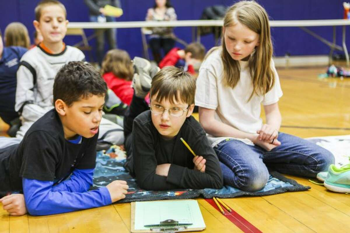 TIME FOR DISCUSSION: After a month of reading, students in fourth through sixth grade competed in the Battle of the Books at Crossroad Charter Academy. Students (from left) Jackson Neglio, Griffin Guernsey and Emma Eckert, quietly discuss their answer before writing it down. (Pioneer photo/Meghan Haas)