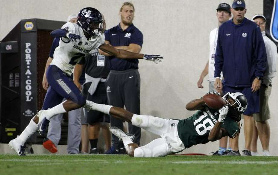 Michigan State's Felton Davis III, right, makes a catch while falling down against Utah State's Ja'Marcus Ingram during the fourth quarter of an NCAA college football game, Friday, Aug. 31, 2018, in East Lansing, Mich. (AP Photo/Al Goldis)