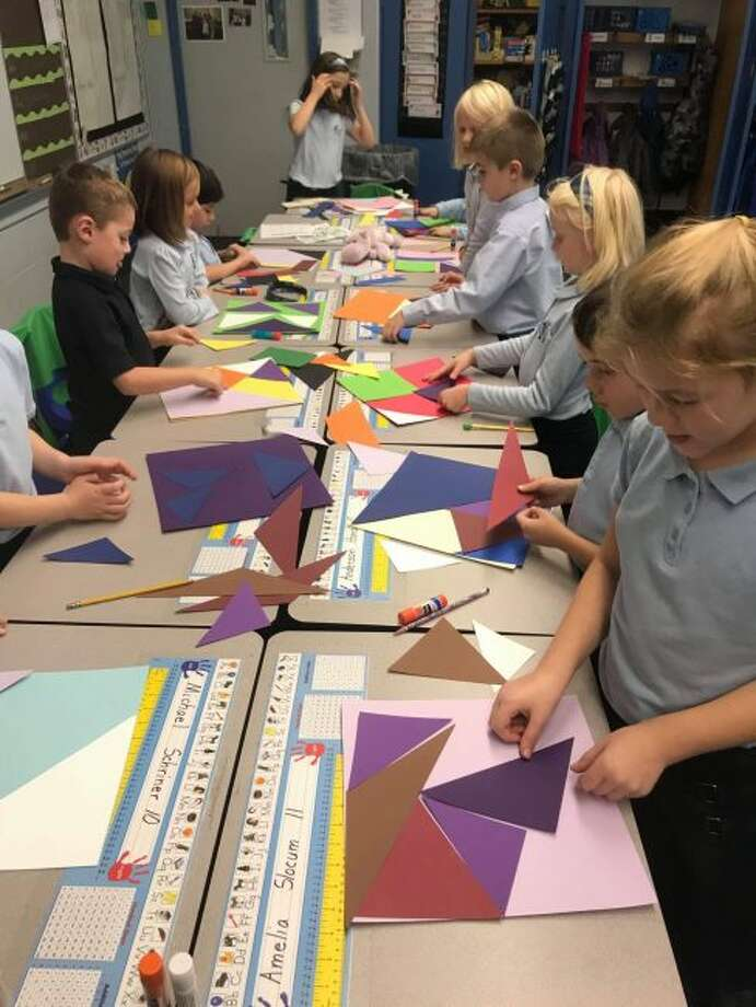 First- and second-graders at St. Mary Catholic School create a quilt to auction off during the 25th annual St. Mary-St. Paul Gala. Proceeds from the gala go toward operating expenses for the school and the Parish Center. (Courtesy photo)