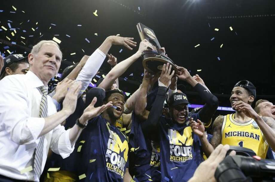 Michigan coach John Beilein, left, and players celebrate after the team's 58-54 win over Florida State in an NCAA men's college basketball tournament regional final Saturday, March 24, 2018, in Los Angeles. (AP Photo/Jae Hong)