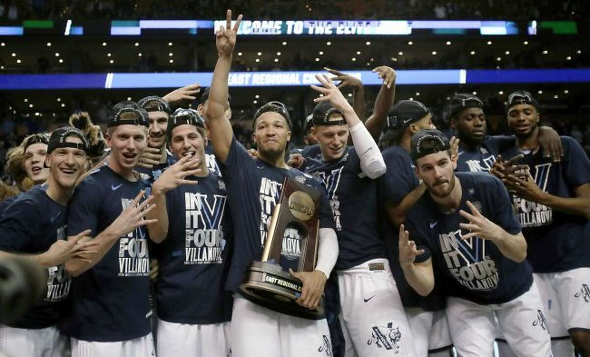 Villanova's Jalen Brunson, center, holding the trophy, celebrates with teammates after their win over Texas Tech in an NCAA men's college basketball tournament regional final, Sunday, March 25, 2018, in Boston. Villanova won 71-59 to advance to the Final Four. (AP Photo/Charles Krupa)