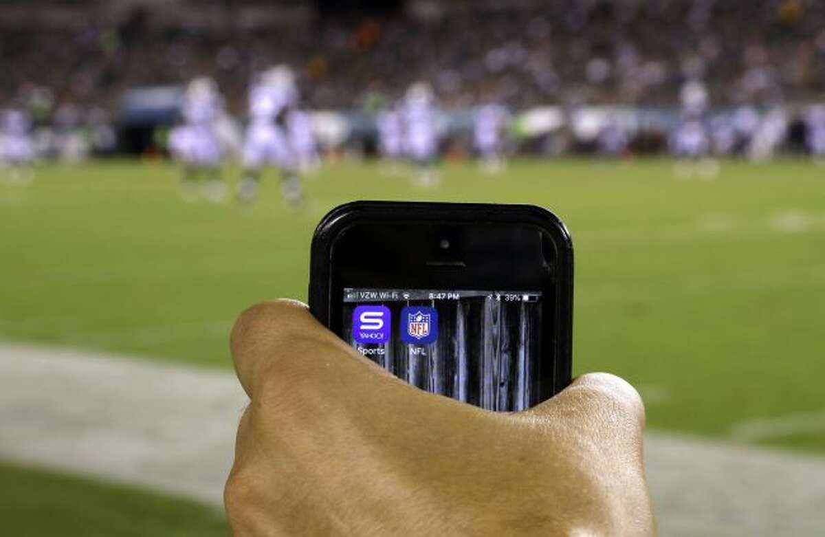 Thursday, Aug. 30, 2018, photo apps for NFL and Yahoo Sports are displayed on a phone on the sidelines before a preseason NFL football game between the Philadelphia Eagles and the New York Jets in Philadelphia. (AP Photo/Matt Rourke)