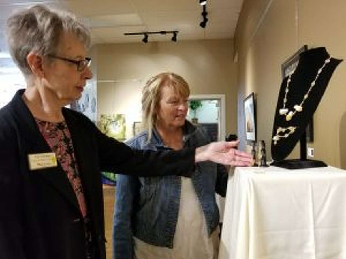 (From left) Pat Heeter, Artworks exhibit coordinator, and Lynne Scheible, Artworks executive director, take a closer look at one of the different pieces on display in the Bevy of Brew Hues exhibit. The work on display throughout the exhibit spans many different mediums.