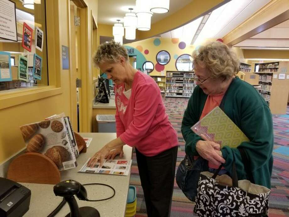 (From left) Deb Macauley, of Morton Township Library's circulation desk, shows community member Joyce Cooker the list of nine books on the 2018 Michigan Notable Books not currently available at the library. The books can be ordered through the Michigan Electronic Library Catalog. (Pioneer photo/Meghan Gunther-Haas)
