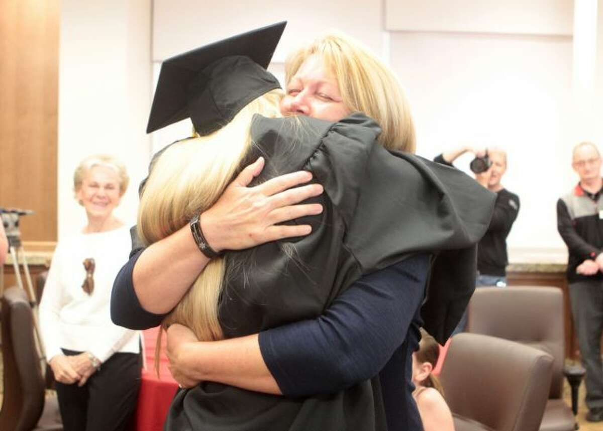Samantha Bates hugs her mom, Tammy, during her surprise hooding ceremony as a graduate of the masters program in the School of Criminal Justice at Ferris State University on Friday. (Pioneer photo/Taylor Fussman)