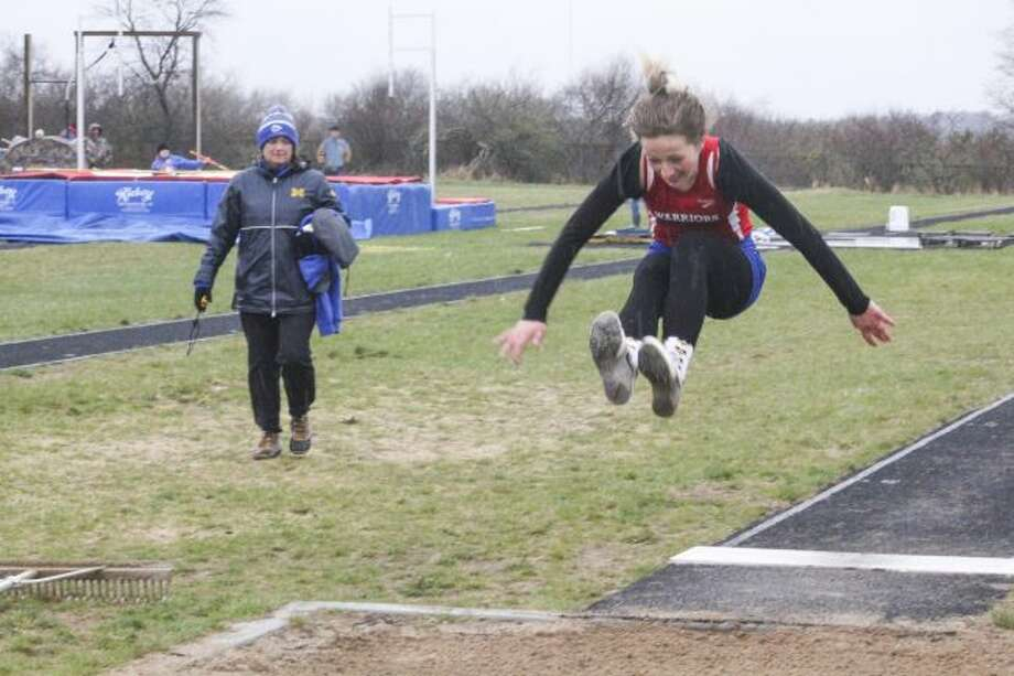 Chippewa Hills girls track coach Sally Schafer (left) watches as Warrior long jumper Kyla Thorne gives the long jump her best effort during the regular season. (Pioneer file photo)
