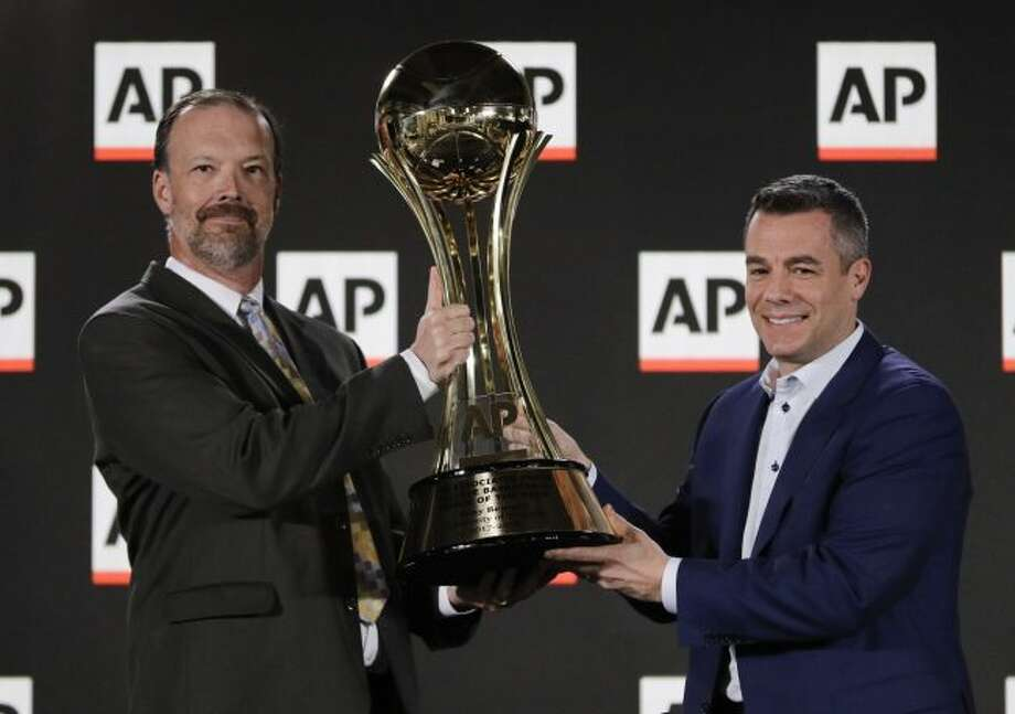 University of Virginia basketball coach Tony Bennett answers questions with his Associated Press Coach of the Year trophy during a news conference at the Final Four NCAA college basketball tournament, Thursday, March 29, 2018, in San Antonio. (AP Photo/David J. Phillip)