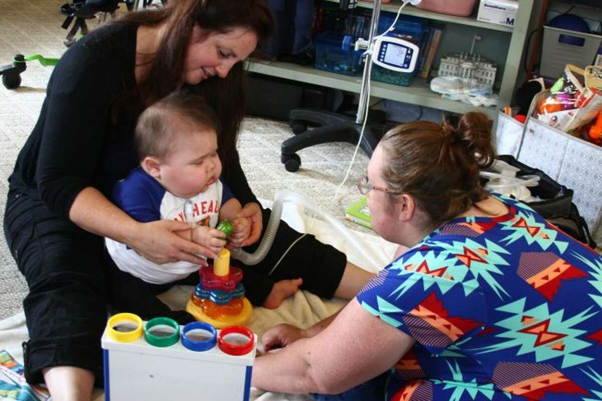 Michelle Seward, physical therapist with Early On, holds Anderson while he plays with his mom, Alicia Moreno. Early On is a program through the MOISD. (Pioneer photos/Emily Grove)