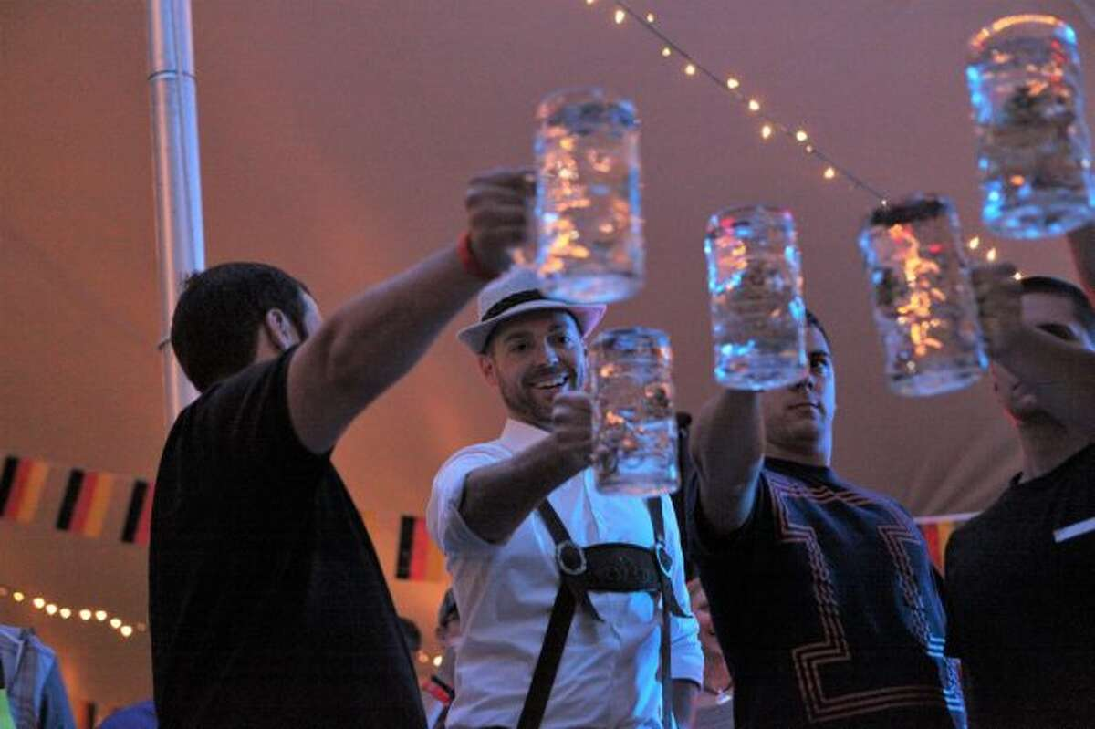 Attendees of last year's Germanfest participate in masskrugstemmen, a game in which contestants hold a liter of liquid ahead of them to see who can hold it the longest. This year, the game is back at the 13th annual Germanfest, set for 6:30 to 11 p.m. on Friday, Sept. 21. (Pioneer file photos)