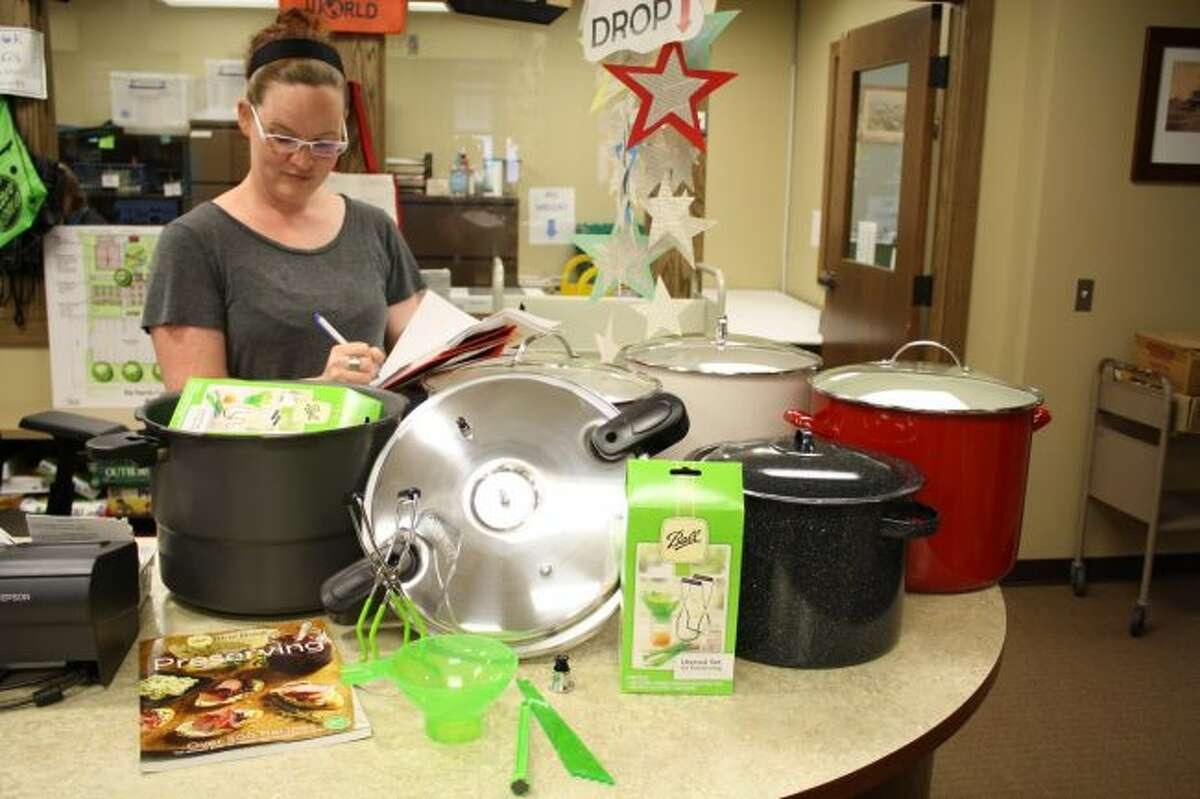 Big Rapids Community Library Director Miriam Andrus checks the inventory of a canner kit. Kits, which include a canner, utensils and basic directions, can be checked out from the library for a week at a time. (Pioneer photo/Candy Allan)