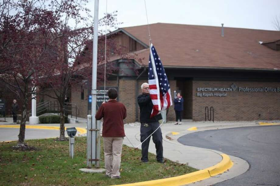 Marsha Manley (left) and Carl Thompson, both Army veterans, performed the raising of the flag during the Veterans Day ceremony at Spectrum Health Big Rapids Hospital on Monday. (Pioneer photos/Taylor Fussman)