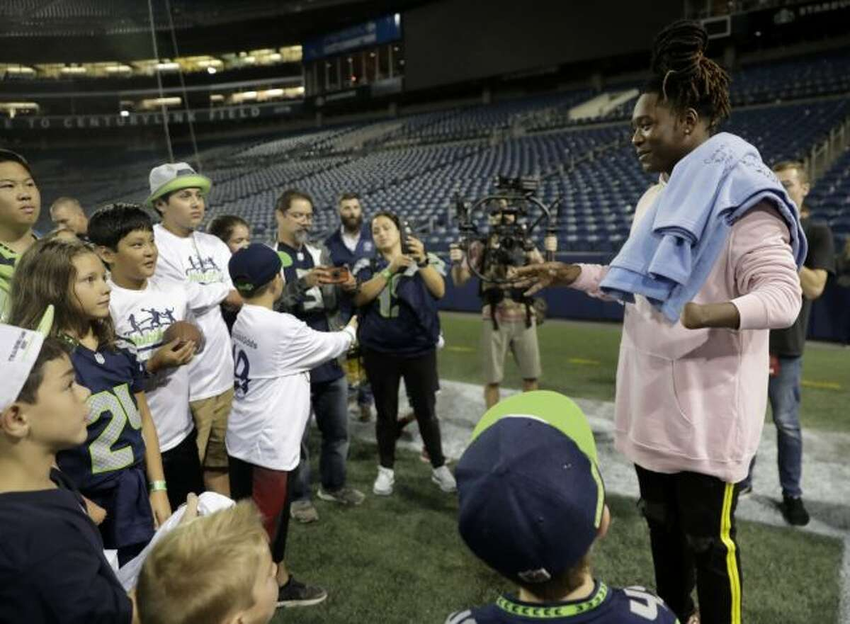 In this Aug. 30, 2018, file photo, Seattle Seahawks linebacker Shaquem Griffin, right, who has only one hand, talks to kids from NubAbility Athletics, a non-profit organization that encourages youth with limb differences to be involved in mainstream sports, following an NFL football preseason game between the Seahawks and the Oakland Raiders in Seattle. Griffin will be one of the starting linebackers for the Seahawks with K.J. Wright out due to minor knee surgery. (AP Photo/Stephen Brashear, File)