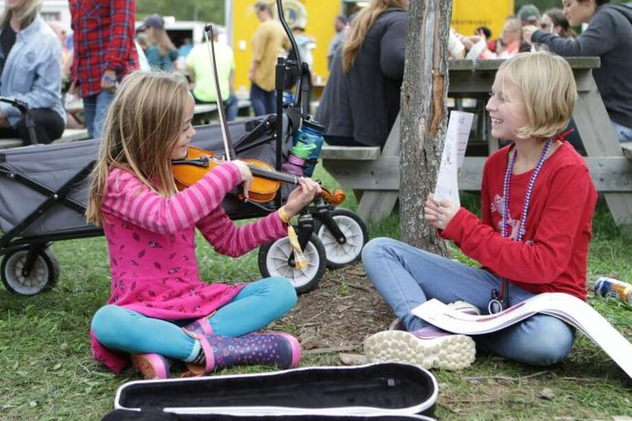 Approximately 14,000 people from around the country spent Friday through Sunday in Remus at the 45th annual Wheatland Music Festival. Across from some of the various craft booths, young Claire Selleck played her violin on Saturday, while Madeline Langlois held the song book. (Pioneer photos/Meghan Gunther-Haas)