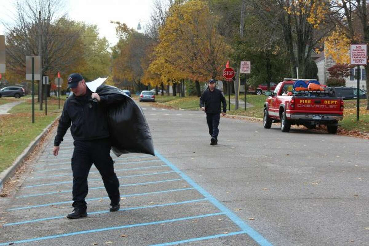 Big Rapids Firefighters Russ Bell and Sean Wethington deliver winter apparel for children at Riverside Elementary School on Wednesday. More than 50 children at local schools received some sort of apparel. (Pioneer photos/Brandon Fountain)