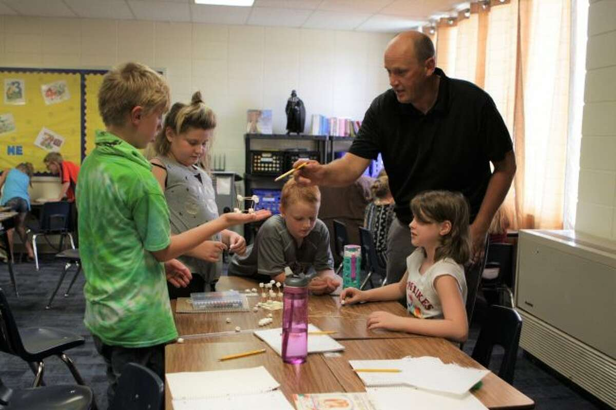 Evart Elementary School teacher Josh Johnston (standing, right) offers tips to fourth-graders during a challenge in their rotation class, which focuses and science, engineering and computer programming. (Pioneer photos/Meghan Gunther-Haas)