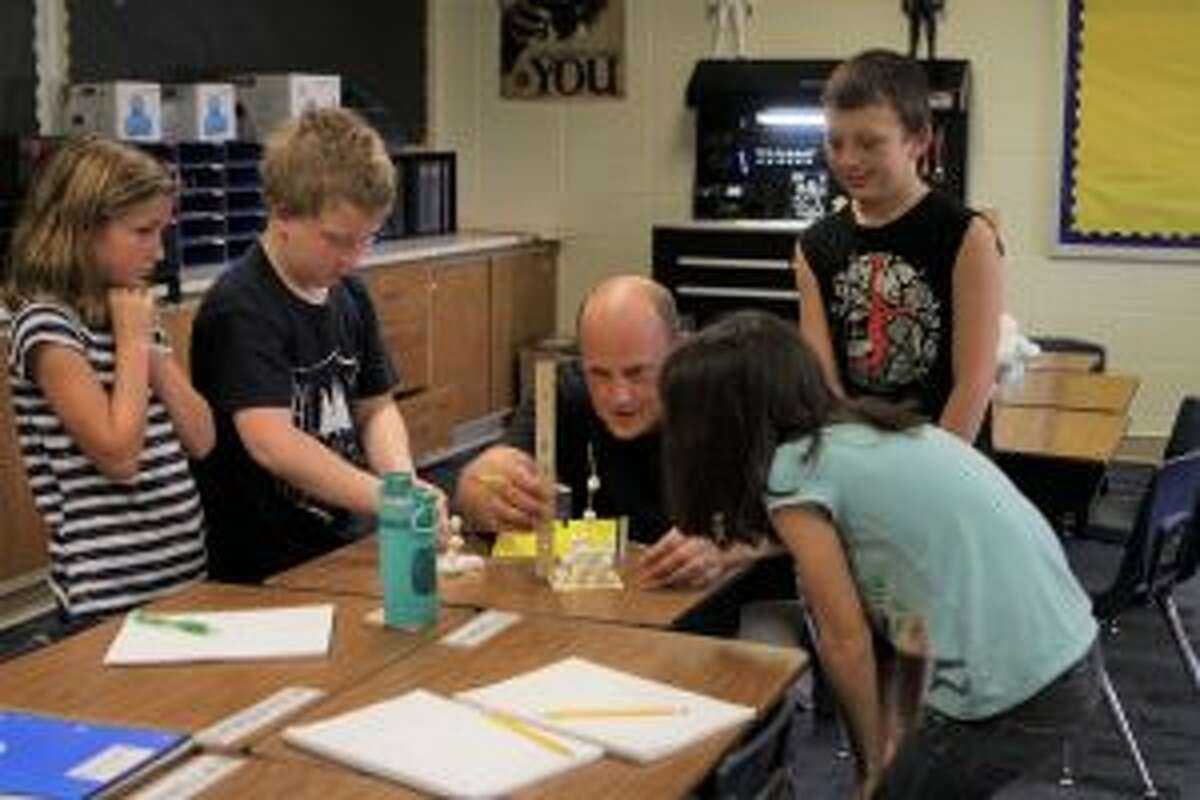 Johnston measures a tower of marshmallows and toothpicks during a classroom challenge. He said his favorite part of his job is working with the students.