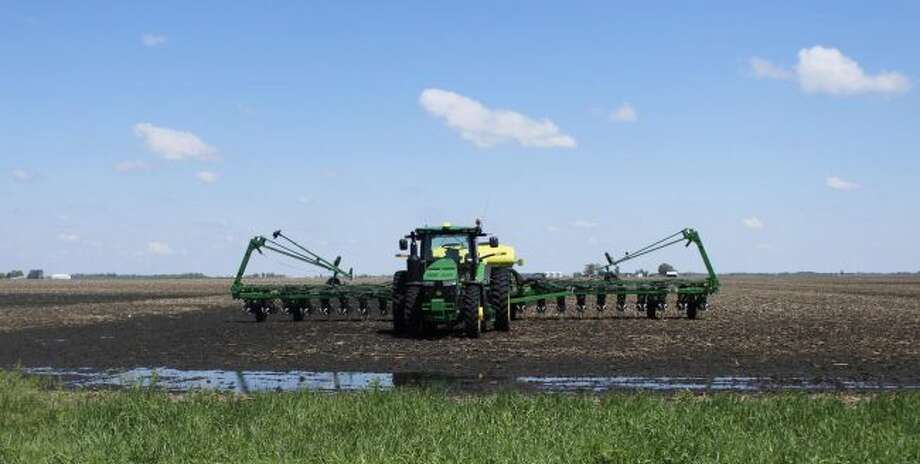 A planter sits in a field that is saturated with water. An extremely wet spring has forced Michigan farmers to wait to get their corn crops planted. (Courtesy photo/Michigan Farm Bureau)