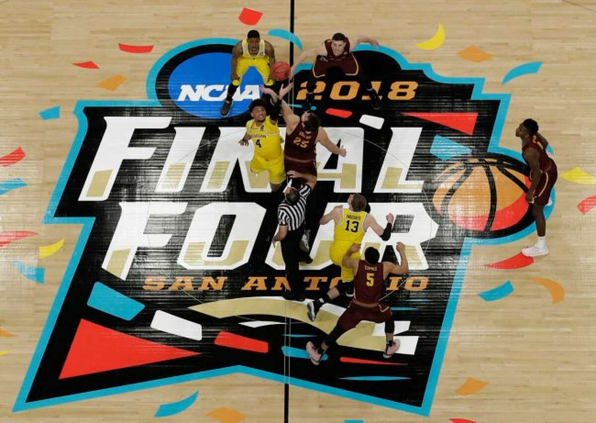 Michigan's Isaiah Livers (4) and Loyola-Chicago's Cameron Krutwig (25) battle for the ball at the tip off during the first half in the semifinals of the Final Four NCAA college basketball tournament, Saturday, March 31, 2018, in San Antonio. (AP Photo/Morry Gash)
