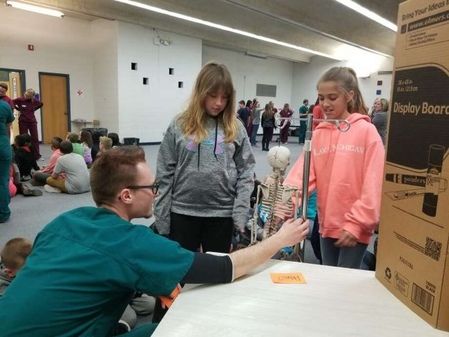 (From left) Ferris State University nuclear medicine program student Joseph Way asks Big Rapids Middle School fifth-graders Brooke Rasmussen and Kate Strasser to identify the pelvic bone during a presentation Monday. Ferris' nuclear medicine and ultrasound program students spent the afternoon sharing with their younger peers how their fields of study contribute to medical diagnoses. (Pioneer photo/Meghan Gunther-Haas)