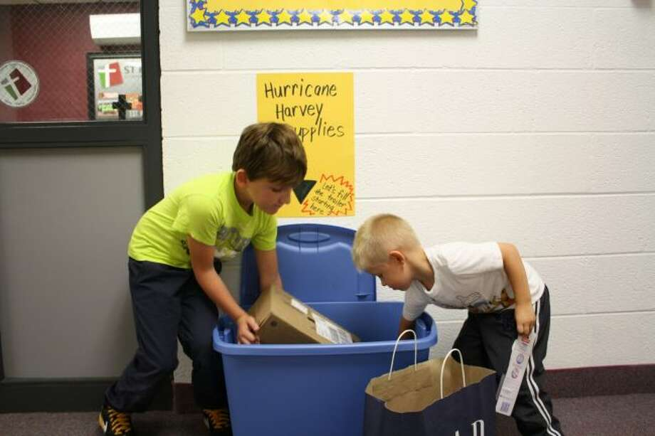 St. Peter's Lutheran School first-grader Jack Lubahn (left) and kindergartener Brayden Britton put donations for hurricane victims in the box outside the school office. St. Peter's is collecting donations this week to take to victims of Hurricane Harvey and Hurricane Irma. (Pioneer photo/Candy Allan)