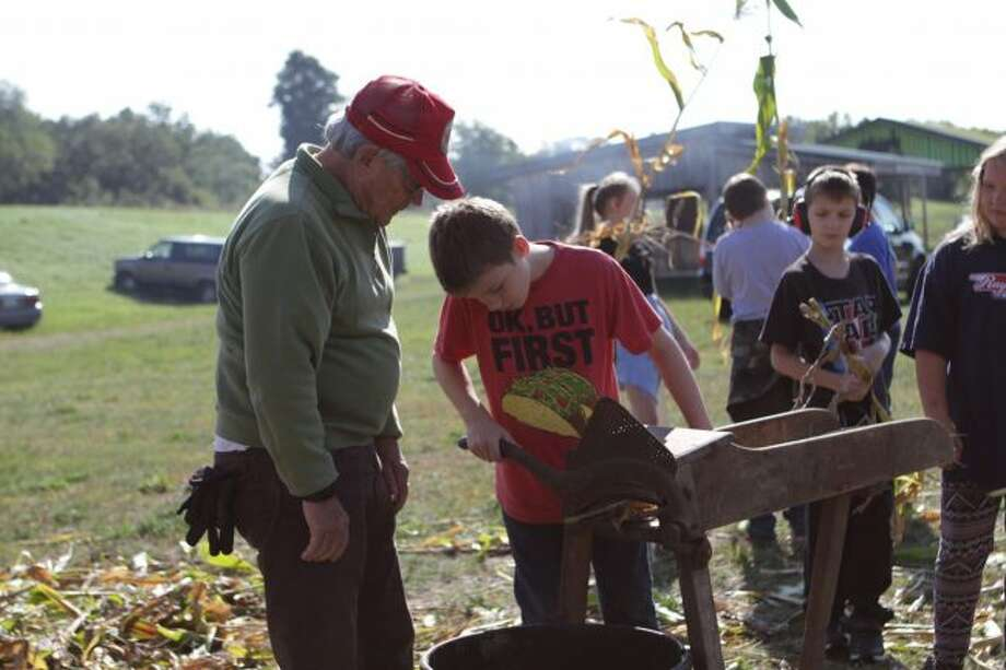 On Tuesday, G.T. Norman Elementary fifth-graders visited the Big Rapids Antique Farm and Power Club grounds to get a hands-on experience with history. (pictured) Dorian Yost chops a corn stalk into smaller pieces, which would be easier for livestock to digest. (Pioneer photos/Meghan Gunther-Haas)