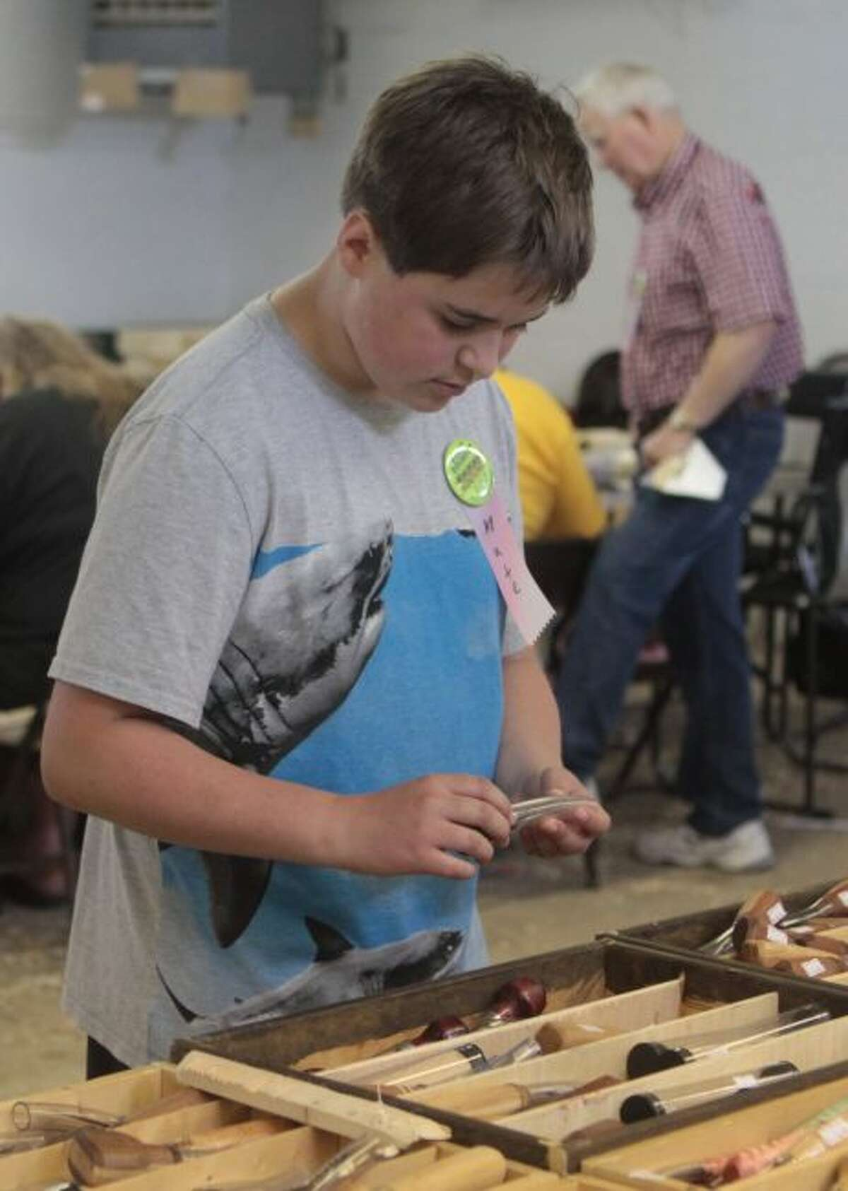 Nathan Southwell looks through a variety of woodcarving tools on display at a vendor booth during the annual Woodcarvers Roundup.