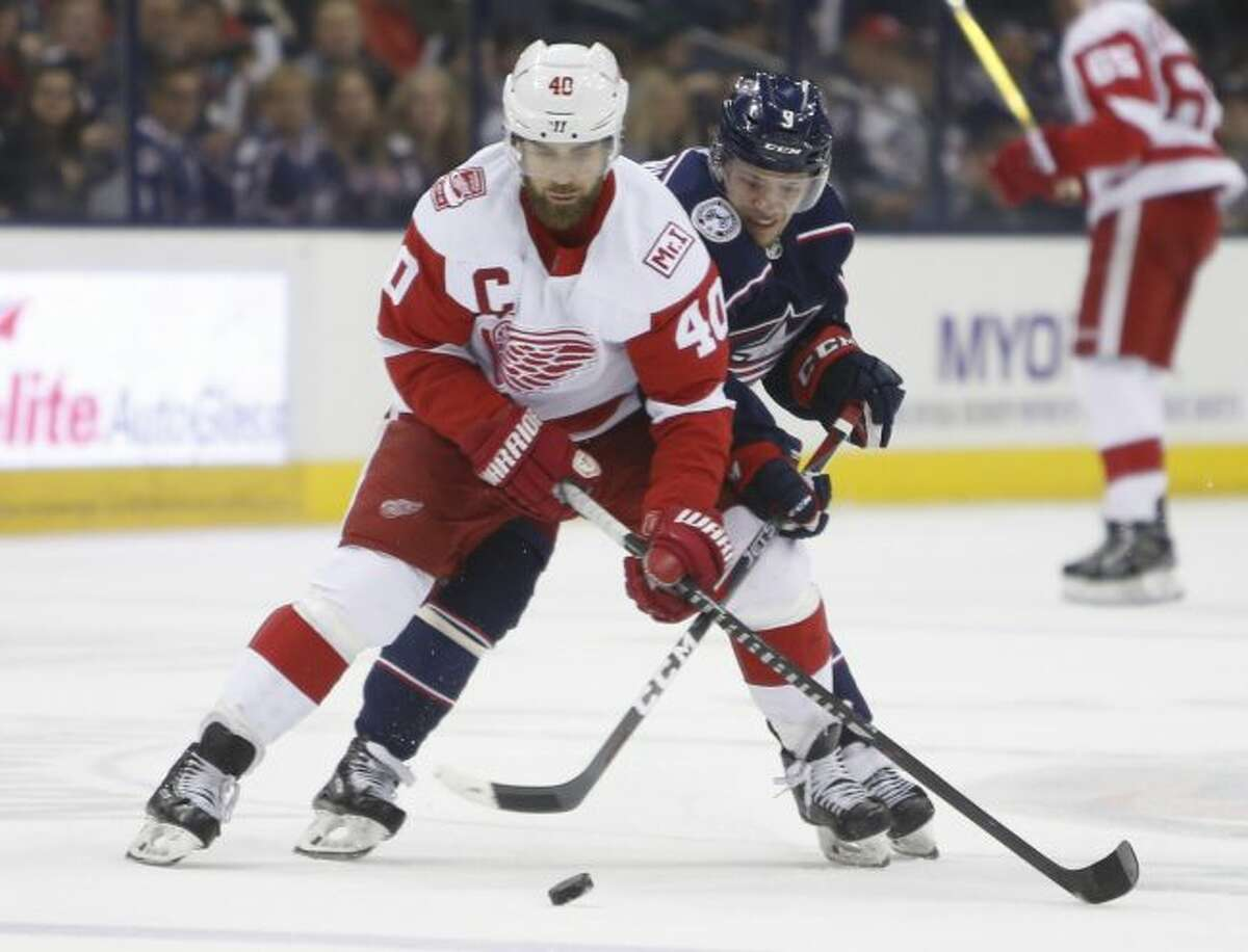 Detroit Red Wings' Henrik Zetterberg, left, of Sweden, carries the puck into the zone during the first period of an NHL hockey game Tuesday, April 3, 2018, in Columbus, Ohio. (AP Photo/Jay LaPrete)