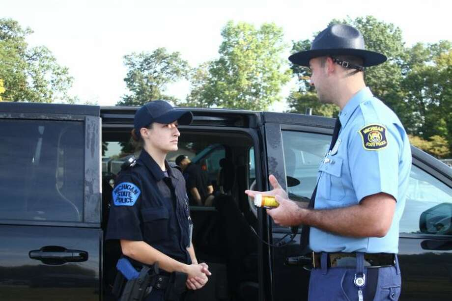 Michelle Cini, a recruit at the Michigan State Police Training Academy in Lansing, listens as Officer Nathan Daugherty explains what to look for if prescriptions are found in a vehicle during a search. Cini is undergoing 19 weeks of training as part of the 22nd Motor Carrier Officer Recruit School. She is one of nine recruits in the program. (Pioneer photo/Emily Grove)
