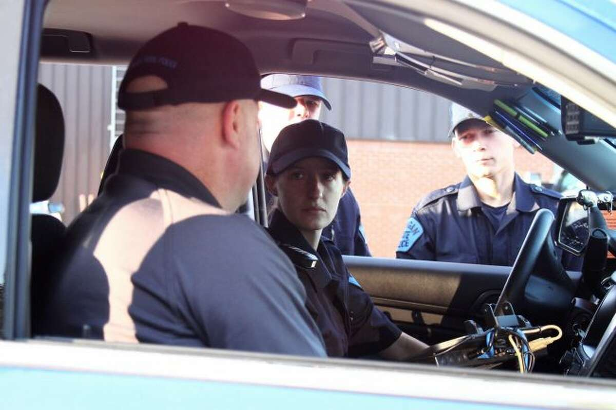 Michelle Cini, a Michigan State Police motor carrier recruit, listens as an instructor goes over the procedure for calling information into dispatch during a traffic stop.