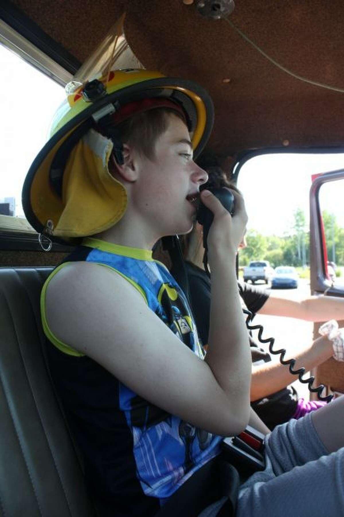 Mecosta-Osceola Intermediate School District Education Center student Devin Wright speaks into a walkie-talkie on a fire truck Friday. (Pioneer photo/Tim Rath)