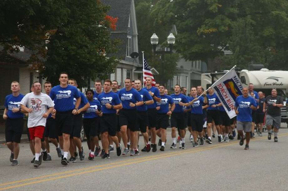 Runner make their way down Michigan Avenue in Big Rapids on Thursday for the Law Enforcement Torch Run. The run raises money and awareness for Special Olympics. (Pioneer photos/Emily Grove)