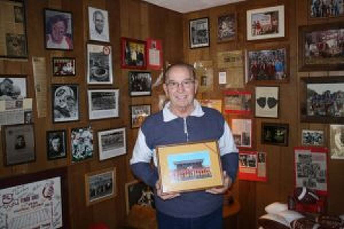 1968 Ferris State football coach Bob Leach holds a picture of his team