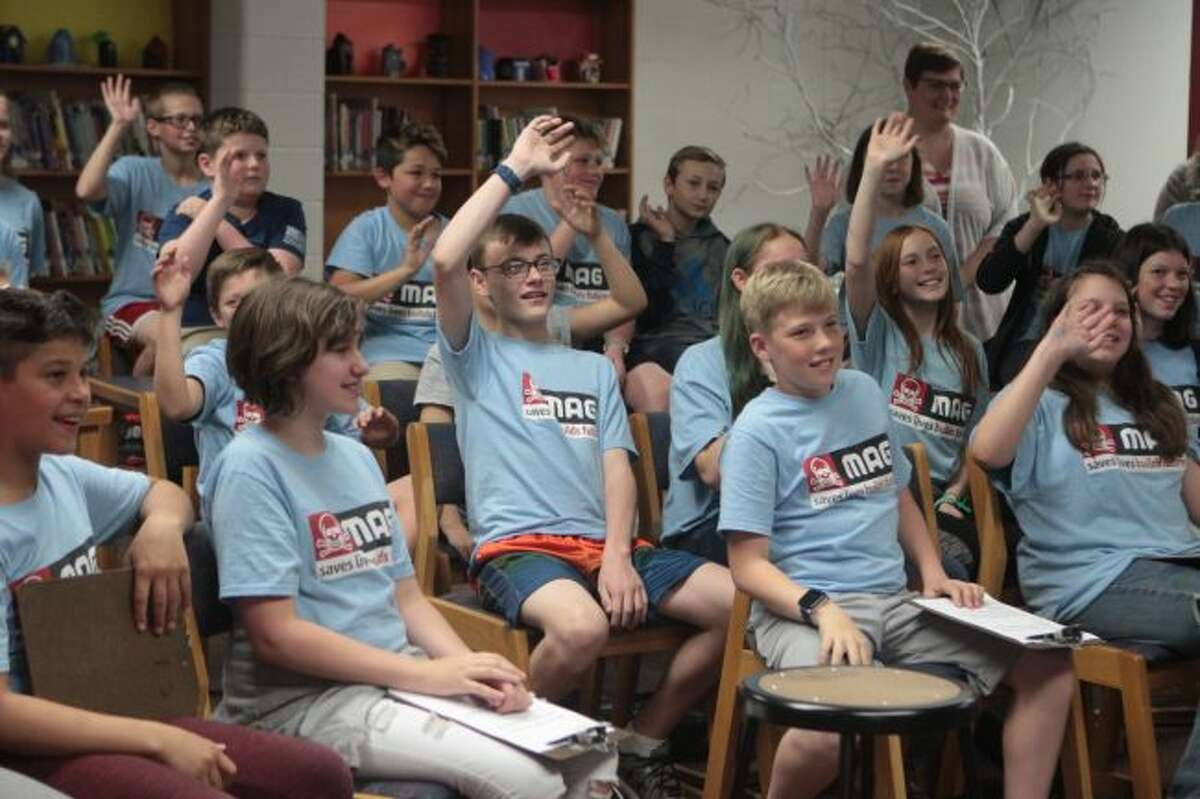Big Rapids Middle School sixth-grade students waive to Rebecca Rusch during a Skype call Tuesday morning.