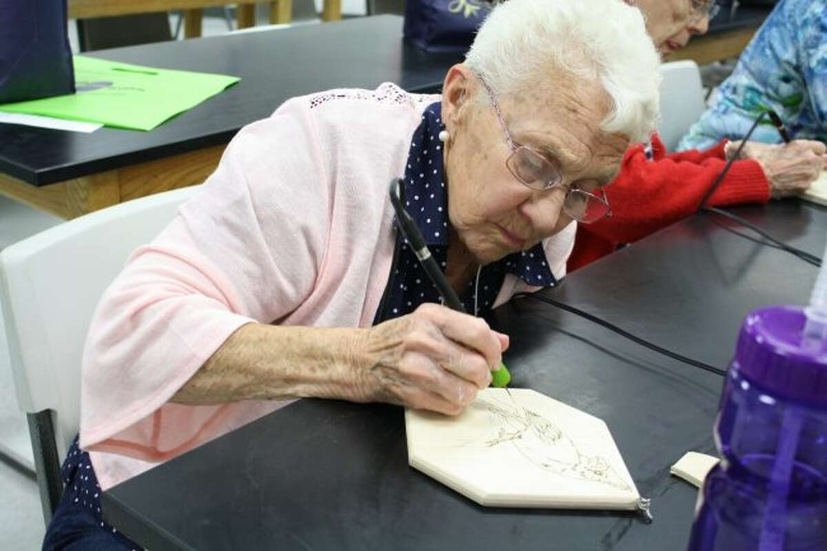 Betty Anderson carefully traces a cardinal with a wood burning tool during Senior Enrichment Day last year. This year's event is scheduled for Wednesday, June 26, at Big Rapids High School. (Pioneer file photo)
