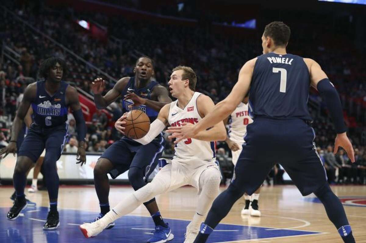 Dallas Mavericks forward Dorian Finney-Smith and center Dwight Powell (7) close in on Detroit Pistons guard Luke Kennard (5) during the first half of an NBA basketball game, Friday, April 6, 2018, in Detroit. (AP Photo/Carlos Osorio)