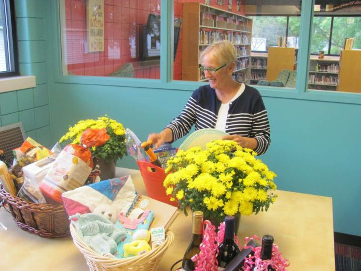 Terry Swier, coordinator of the Champagne and Chocolate Gala, arranges a basket for the silent auction for the gala, which will take place Friday, Sept. 22, at Morton Township Library. (Courtesy photo)