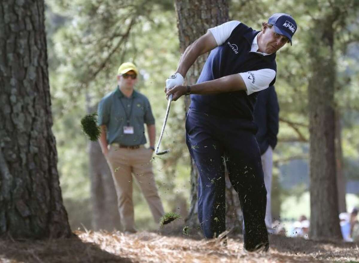 Phil Mickelson hits out of the woods off of the first fairway during the second round of the Masters golf tournament at Augusta National Golf Club in Augusta, Ga., Friday, April 6, 2018. (Curtis Compton/Atlanta Journal-Constitution via AP)