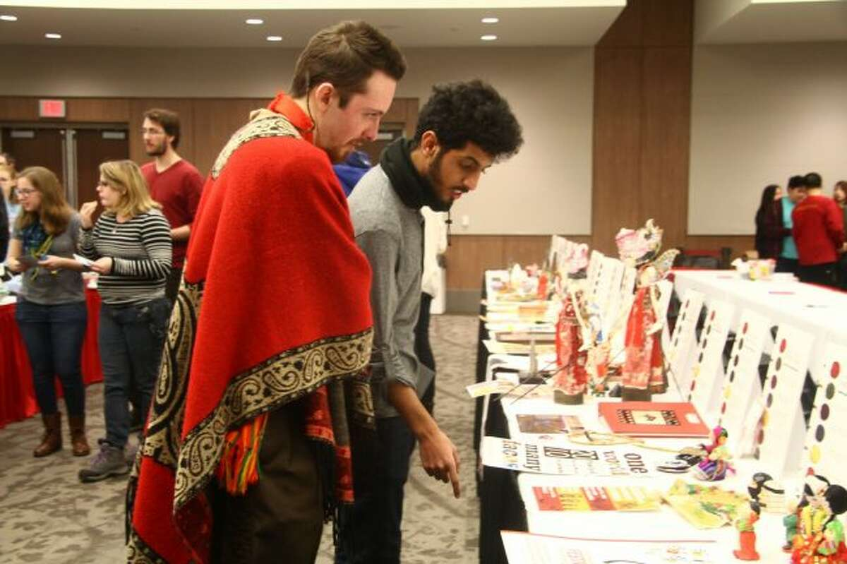 Guilherme Sudbrack, of Brazil, and Sultan Alghanim, of Saudi Arabia, look at a table of cultural items from various countries.