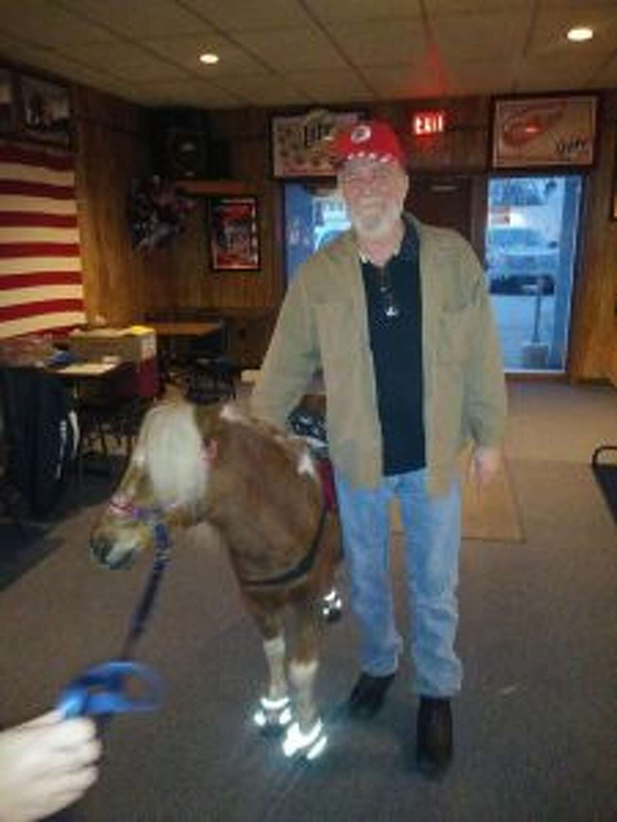Bob McCall poses with Charlie, the miniature American horse and mascot for Mid-Michigan Honor Flight. (Courtesy photo)