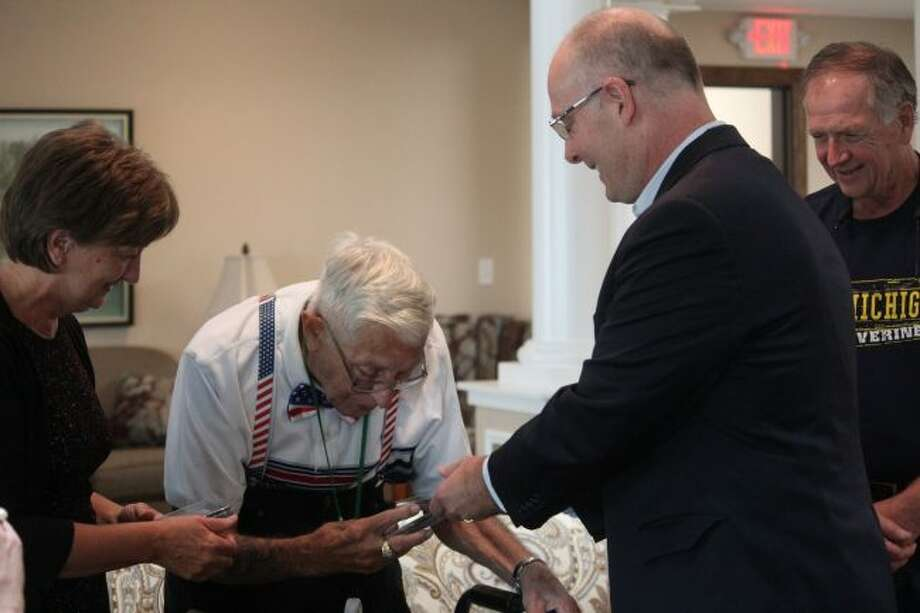 U.S. Rep. John Moolenaar presents World War II veteran Harry Morse with medals he earned during his time in the U.S. Navy during World War II during a ceremony Tuesday afternoon at Reed City Fields Assisted Living Facility. Morse served as an electrician's mate on the USS Herndon during the D-Day invasion. (Pioneer photos/Brandon Fountain)