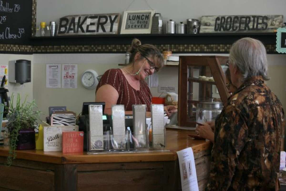 Jan Cassidy, owner of The Yellow Window and Little Brown Sack Deli, assists customers at her store's new location on South Michigan Avenue. Cassidy said the new building has been a good fit for her business. (Pioneer photo/Taylor Fussman)