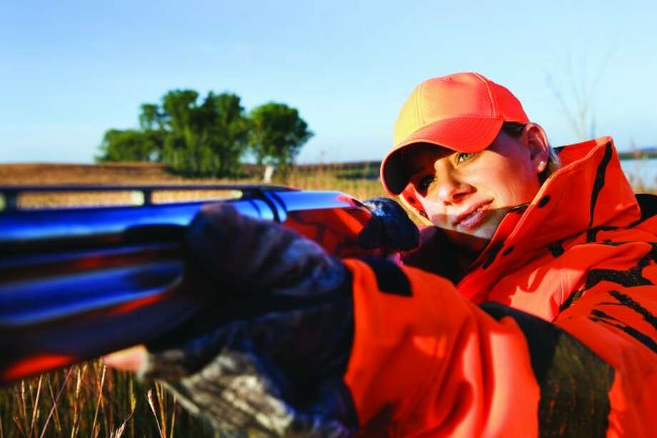 """A hunter wears clothing items that are """"hunter orange."""" Recently, the Michigan Natural Resources Commission ruled against adding pink as an allowable safety color. (Courtesy photo)"""