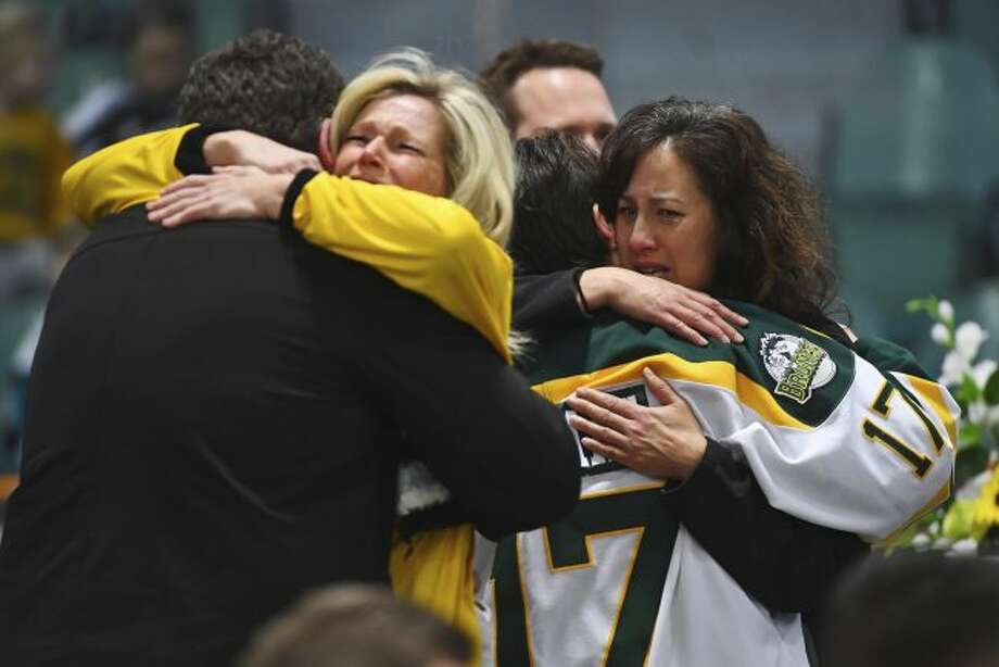 Mourners comfort each other as people attend a vigil at the Elgar Petersen Arena, home of the Humboldt Broncos, to honor the victims of a fatal bus accident in Humboldt, Saskatchewan on Sunday, April 8, 2018. (Jonathan Hayward/The Canadian Press via AP)