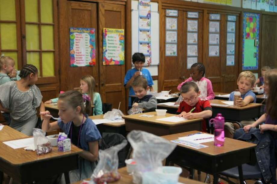 After filing into class for the day, students at Barryton Elementary School sit down with their breakfasts and a begin a worksheet. Students who come to school hungry are more likely to act out in class or have difficulty focusing on their lessons. (Pioneer photos/Meghan Haas)