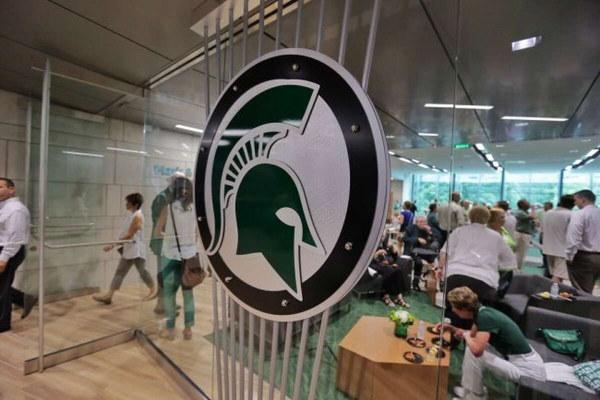In this Aug. 25, 2014, file photo, people tour the new North End Zone Complex renovations at Spartan Stadium on the Michigan State Campus in East Lansing, Mich. A woman who attends Michigan State University filed a federal lawsuit against the school Monday, April 9, 2018, alleging that three former men's basketball players sexually assaulted her at an off-campus apartment in 2015 and that she was discouraged from reporting what happened. (Ryan Garza/Detroit Free Press via AP, File)